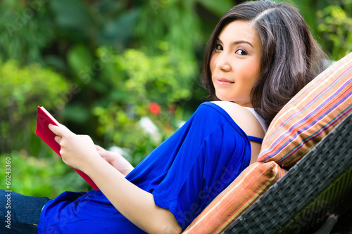 Young Asian woman at home in garden