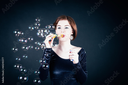 Young woman making soap bubbles