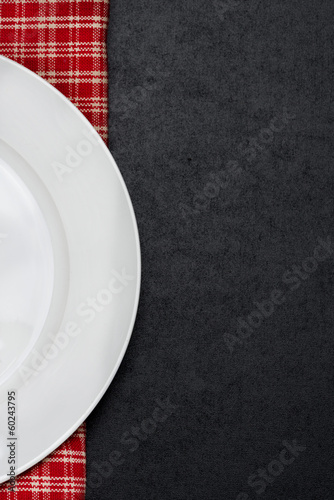empty plate on a checkered napkin and black background