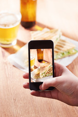 Smartphone taking photo of feta cheese sandwich