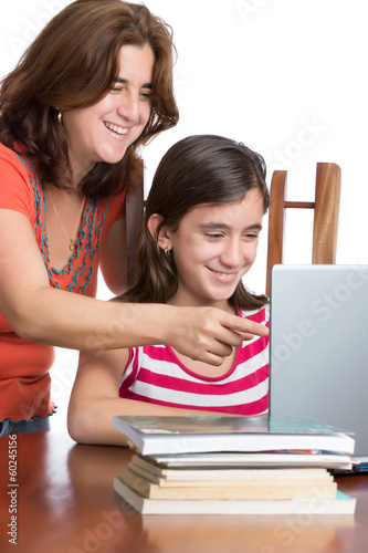 Hispanic teen and her mother browsing the web and laughing