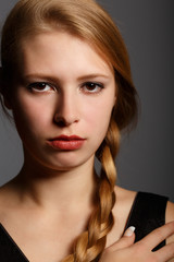 Beautiful young woman with stern look and plait hairstyle