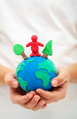 Ecology concept with clay world globe in child hand