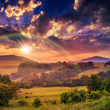 cold fog on hot sunrise in mountains with rainbow
