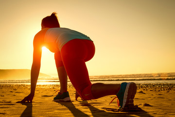 Woman ready for running on sunset beach
