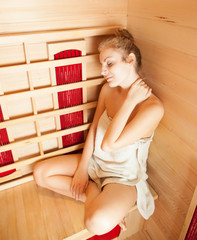 Young woman relaxing in a sauna (color toned image)