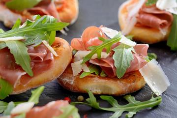 Pizzasnack mit Schinken, Rucola und Parmesan