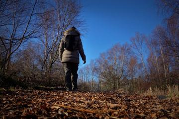 A woman walking through woodland