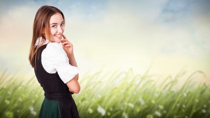 lächelnde junge Frau im Dirndl vor Sommerwiese