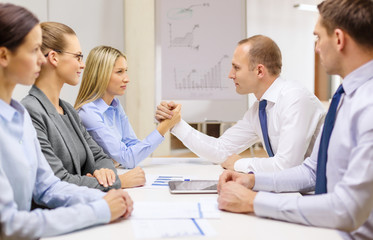 businesswoman and businessman arm wrestling