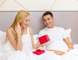 man giving woman little red gift box