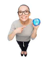 woman in eyeglasses pointing finger to blue clock