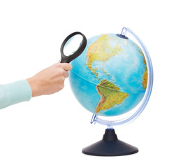 woman hand holding magnifying glass over globe