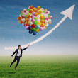 Businesswoman flying high with helium balloons