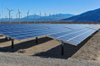 Solar panels in front of wind turbines and mountians - 60257784