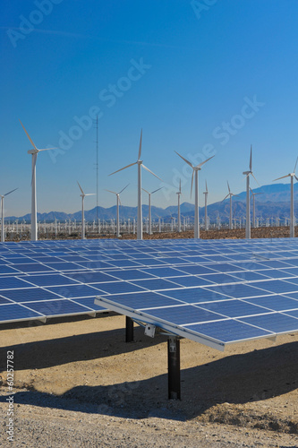 Solar panels in front of wind turbines and mountians