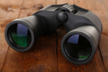 Black modern binoculars on wooden background