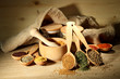 Assortment of spices in wooden spoons and jars,