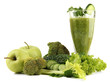 Glass of green vegetable juice and vegetables isolated on white
