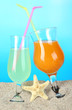 Beach cocktails in sand on blue background