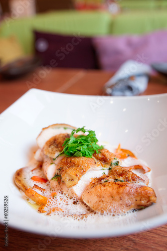Chicken breast with baby vegetables on plate