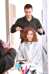 Young man hairdresser do hairstyle girl in beauty salon