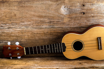 ukulele against a wooden background.