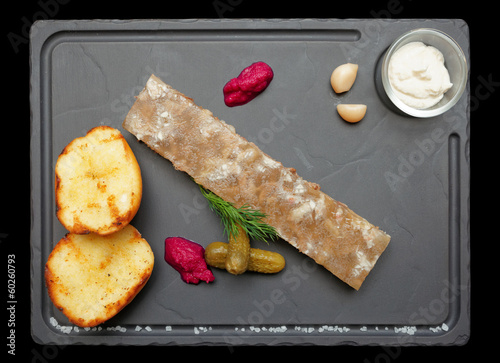 Meat aspic with potatoes and horseradish isolated on black