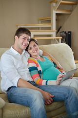 pregnant couple at home using tablet computer