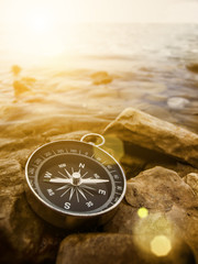 compass on the shore at sunrise