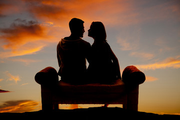 silhouette couple facing on a bench