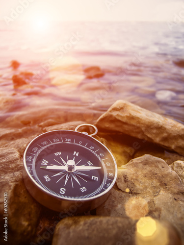 compass on the shore with sun fare