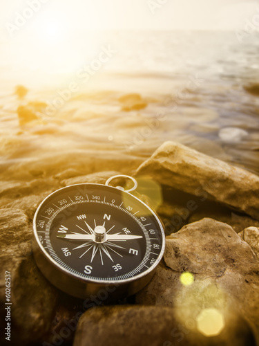 Leinwanddruck Bild compass on the shore at sunrise