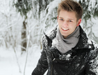 handsome smiling young man posing in winter park.