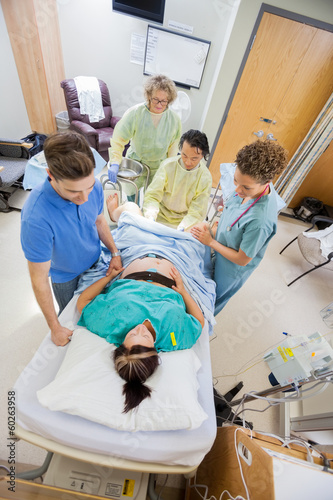 Doctors With Nurse Operating Pregnant Woman During Delivery