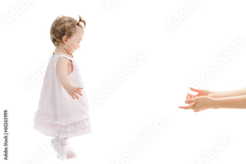 Isolated first steps of cute baby girl to her mother's arms