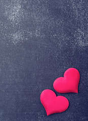 two red hearts on a black board