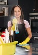 Beautiful cheerful brunette woman in gloves cleaning kitchen