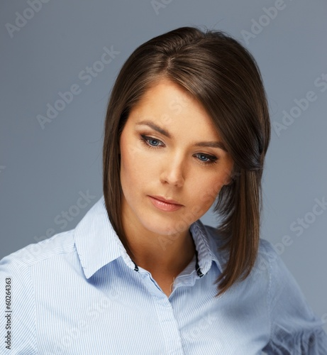 Thoughtful beautiful young brunette woman in blue shirt