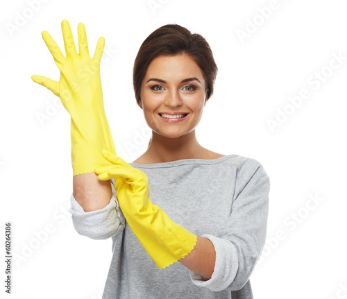 Beautiful cheerful brunette woman pulling on rubber gloves