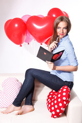 Beautiful young woman with heart shaped balloons writing a love