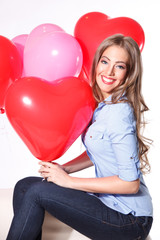 Portrait of a beautiful young woman with heart shaped balloons a