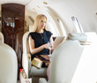 Rich Woman Using Tablet Computer In Private Jet