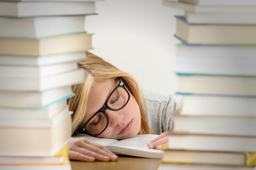Student girl sleeping between pile of books