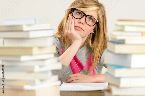 Bored student girl between stack of books