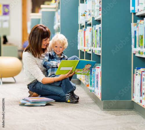 Boy And Teacher Reading Book By Bookshelf