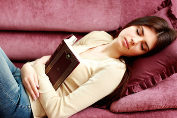 Young beautiful woman sleeping with book on the sofa at home