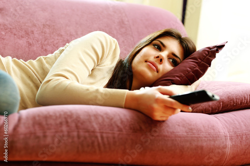 woman lying on the sofa with remote control at home