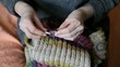 Woman hands knitting wool scarf, closeup video