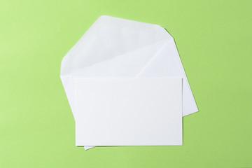 Sobre y tarjeta en blanco sobre fondo verde